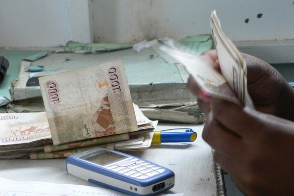 Kenyan with money and a mobile banking tool, photo by Scott Mainwaring/CC BY 2.0