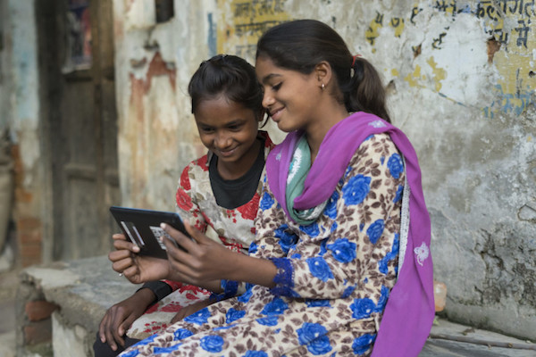 Indian girls work on a tablet computer provided by Pratham USA, photo by courtesy Pratham