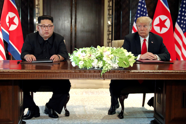 U.S. President Donald Trump and North Korea's leader Kim Jong Un hold a signing ceremony at the conclusion of their summit at the Capella Hotel on the island of Sentosa, Singapore, June 12, 2018, Photo by Jonathan Ernst/Reuters