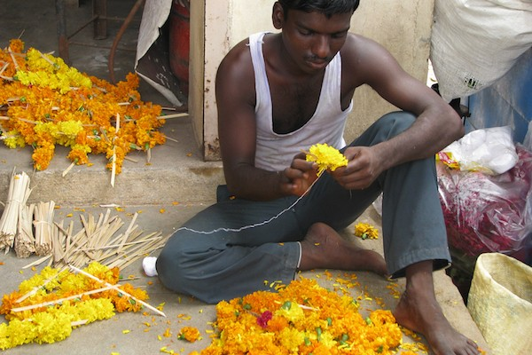 Young Indian man makes flower garlands for sale, photo by McKay Savage/CC BY 2.0
