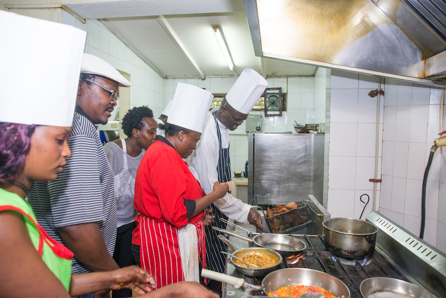Participants using the deep fryer in the kitchens of Golf Course Hotel