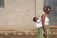 African women walks with baby on back
